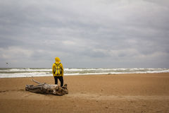 Men in yellow raincoat on the beach looking at storm. Stock Photos