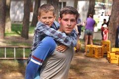 Mena, Ukraine - 11. Mai 2018: Der Sportkerl h?lt einen kleinen Jungen auf seinem zur?ck Im Freienspiele freizeit lizenzfreie stockfotos