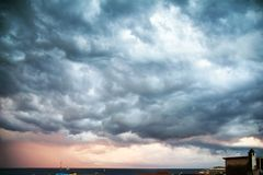 Menacing clouds over the sea. Storm clouds that the northwest wind leads over the village at sunset royalty free stock photos