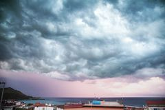 Menacing clouds over the sea. Storm clouds that the northwest wind leads over the village at sunset stock photography