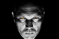 Menacing looking man with orange eyes Stock Image