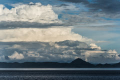 Menacing Lovely Clouds Over The Dark Blue Hills Near The Calm Ocean Singapore Royalty Free Stock Photos