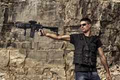 Menacing man pointing a machine gun Stock Images