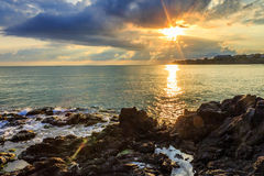 Menacing morning sea landscape with rocky coast and rising sun r Stock Photo
