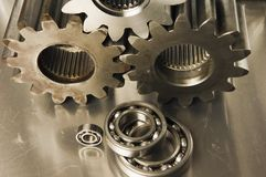 Menagerie of metals. Cog-wheels and bearings against brushed aluminum Royalty Free Stock Image