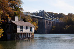 Menai Bridge and a house on the foreshore. Views along the Menai Straits from the Isle of Anglesey North Wales Stock Photos
