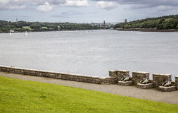 Menai Strait from Anglesey, Wales, UK. With three cannons in foreground and Britannia Bridge and surrounding coastal countryside in backgrounod Stock Photos