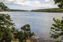 Menai Strait from shore on Anglesey, Wales, UK. With coastlines and Britannia Bridge in background Stock Photo