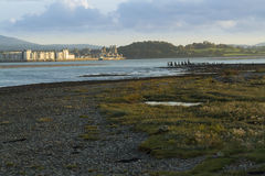 Menai Straits and Caernarfon at Sunset. Looking East across the Menai Straits to Snowdonia and Caernarfon with its castle, from Anglesey, North Wales, United Royalty Free Stock Image
