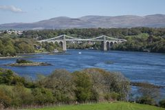 The Menai Suspension Bridge, Wales - sunny day, blue waters. . The Menai Suspension Bridge is a suspension bridge to carry road traffic between the island of Stock Image