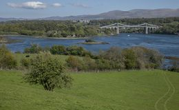 The Menai Suspension Bridge, Wales - sunny day, green meadows. The Menai Suspension Bridge is a suspension bridge to carry road traffic between the island of Stock Photography