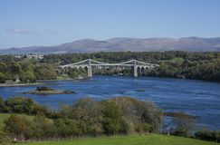 The Menai Suspension Bridge, Wales - the view. The Menai Suspension Bridge is a suspension bridge to carry road traffic between the island of Anglesey and the Royalty Free Stock Photography