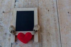 Menübrett im schwarzen und roten Herzen und ein menschlicher Schädel legen auf das w Stockfotos