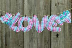 Menchie, błękitny miłość tekst i serca wiesza na clothesline podławym drewna ogrodzeniem i Zdjęcia Stock