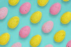 Menchie i żółci Wielkanocni jajka w powtórka wzorze na błękitnym tle fotografia stock