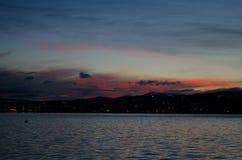 Menchie i kolorowy jutrzenkowy niebo nad tromsoe miasta wyspą z odbiciem na błękitnym fjord Obraz Royalty Free