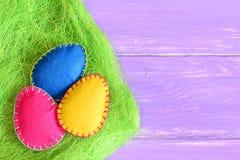 Menchie, kolor żółty i błękitni odczuwani Wielkanocni jajka w trawie zielony sizalu włókno na purpurowym drewnianym tle z kopii p Obraz Stock