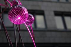 Menchie spotlighted lustrzane piłki przed ciemnym kamienistym biznesowym budynkiem Zdjęcie Royalty Free