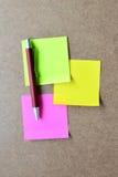 Menchie, zieleń, żółty nutowy papier i czerwony pióro na drewnianym tle, Obraz Royalty Free