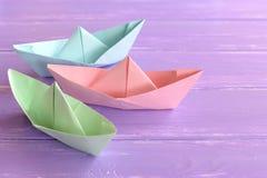 Menchie, zieleń, błękitnego papieru łodzie na lilym drewnianym tle Papierowe falcowanie techniki Łatwi origami rzemiosła dla dzie obrazy stock
