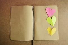 Menchie, zieleń, koloru żółtego papierowy kierowy kształt na starym strony książki pustym miejscu Obrazy Stock