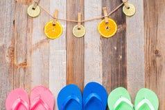 Menchii, błękitnych i zielonych trzepnięcie klapy sandały na drewnianym tle, zdjęcia stock