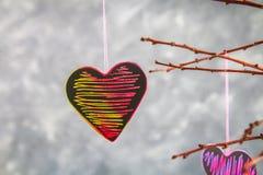 Menchii serca wieszają na gałąź na szarość betonu tle odosobnionego loga miłości przedmiota znaka drzewny warianta wektor Pojęcie Zdjęcie Royalty Free