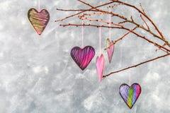 Menchii serca wieszają na gałąź na szarość betonu tle odosobnionego loga miłości przedmiota znaka drzewny warianta wektor Pojęcie Fotografia Stock