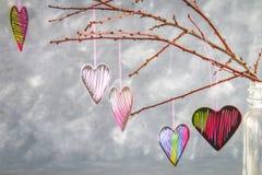 Menchii serca wieszają na gałąź na szarość betonu tle odosobnionego loga miłości przedmiota znaka drzewny warianta wektor Pojęcie Zdjęcie Stock
