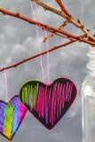 Menchii serca wieszają na gałąź na szarość betonu tle odosobnionego loga miłości przedmiota znaka drzewny warianta wektor Pojęcie Obraz Royalty Free
