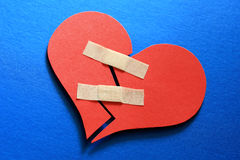 Mend a broken heart. Broken heart fixed with adhesive bandage stock photo