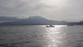 Mendeleev volcano. Two boats against the backdrop of the volcano stock footage