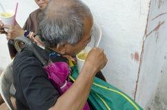 Mendiant d'abat-jour de vieil homme mangeant une tasse de gruau Image libre de droits