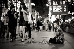 Mendiant et femme riche dans un secteur de achat à Singapour images libres de droits