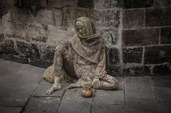 Mendiant s'asseyant près d'un mur photo stock