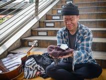 Mendiant sale de visage sur la rue regardant l'argent et souriant avec sa guitare à coté photographie stock