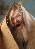 Mendicant. Portrait old beggar with a beard and mustache, wrapped in burlap, with pain and despair in his eyes, the studio on a brown-blue background Royalty Free Stock Photography
