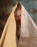 Mendicant. Portrait old beggar with a beard and mustache, wrapped in burlap, with pain and despair in his eyes, the studio on a brown-blue background Royalty Free Stock Photos
