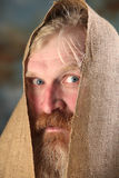 Mendicant. Portrait old beggar with a beard and mustache, wrapped in burlap, with pain and despair in his eyes, the studio on a brown-blue background Stock Image