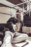 Mendicante che individua sulle scale del sottopassaggio e che prova ad elemosinare fotografie stock