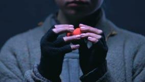Mendicante che tiene il giocattolo del cuore, simbolo di carità, aiuto al barbone, primo piano stock footage