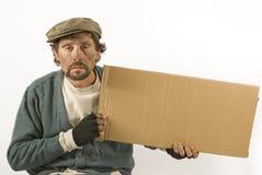 Mendicante con cartone ed il berreto Fotografia Stock Libera da Diritti