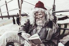 Mendicante recontando o lote do livro ao transeunte ao ler fotos de stock royalty free