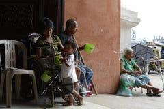 Mendicante sulla sedia a rotelle accanto all'uomo cieco che per mezzo del cellulare al portale del portone della porta della chie immagini stock