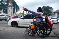 mendigo da cadeira de rodas que guarda a esmola procurando da caixa de presente do Natal no portal da porta da igreja Fotos de Stock