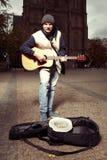 Mendigo de canto com a guitarra na frente da igreja foto de stock royalty free