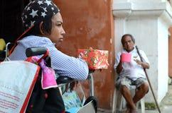 mendigo de la silla de ruedas que celebra limosnas que buscan de la caja de regalo de la Navidad en el portal de la puerta de la  Fotografía de archivo
