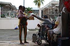 mendigo de la silla de ruedas que da pelotillas del pan al niño de abrazo de la mujer embarazada como regalo durante tiempo de la fotos de archivo
