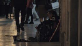 Mendigo del hombre que se sienta en calle muy transitada almacen de metraje de vídeo