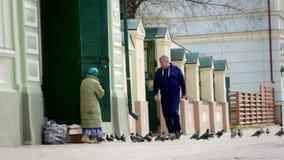 Mendigo desabrigado do homem e do russo perto da igreja cristã vídeos de arquivo